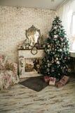 Árbol de navidad y chimenea con una butaca Imagen de archivo libre de regalías