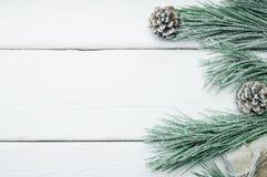 Árbol de navidad y cono de la rama con nieve en la opinión superior del fondo de madera blanco del vintage imagenes de archivo