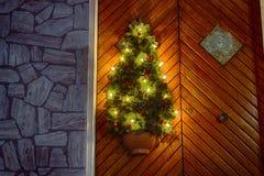 Árbol de navidad y luces en puerta de madera Imágenes de archivo libres de regalías