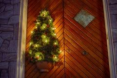 Árbol de navidad y luces en puerta de madera Imagenes de archivo