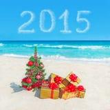 Árbol de navidad y regalos de oro en la playa del mar Concepto para nuevo YE Imagen de archivo libre de regalías