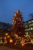 Árbol de navidad y renos al lado de un buil público Imágenes de archivo libres de regalías