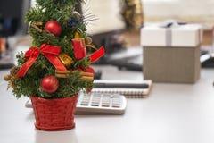 Árbol de navidad y una caja de regalo en el lugar de trabajo el Nochebuena Imagenes de archivo