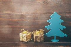 Árbol decorativo del Año Nuevo con cajas festivas en papel brillante del oro Foto de archivo