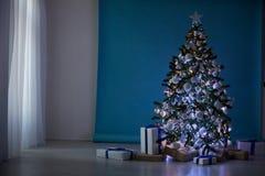 Árbol del Año Nuevo en las guirnaldas de la Navidad en fondo blanco azul azul Fotos de archivo libres de regalías