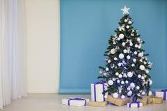 Árbol del Año Nuevo en las guirnaldas de la Navidad en fondo blanco azul azul Fotografía de archivo