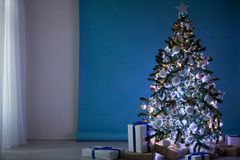 Árbol del Año Nuevo en las guirnaldas de la Navidad en fondo blanco azul azul Fotografía de archivo libre de regalías