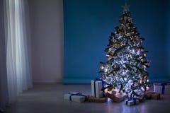 Árbol del Año Nuevo en las guirnaldas de la Navidad en fondo blanco azul azul Imagen de archivo libre de regalías