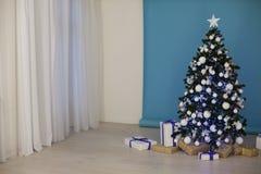 Árbol del Año Nuevo en las guirnaldas de la Navidad en fondo blanco azul azul Fotos de archivo