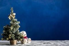 Árbol del Año Nuevo y cachorro de oso en la arena blanca y el fondo azul Fotos de archivo