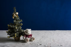 Árbol del Año Nuevo y cachorro de oso en la arena blanca y el fondo azul Foto de archivo