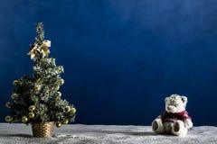 Árbol del Año Nuevo y cachorro de oso en la arena blanca y el fondo azul Fotos de archivo libres de regalías