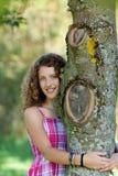 Árbol del abarcamiento de la chica joven en parque Fotos de archivo libres de regalías