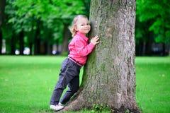 Árbol del abarcamiento de la muchacha del oflittle del retrato en parque Imagenes de archivo
