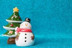 Árbol del muñeco de nieve y de pino en fondo chispeante Estación de la Navidad Imágenes de archivo libres de regalías