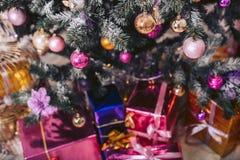 Árbol del ` s del Año Nuevo adornado con los juguetes con las cajas de regalo debajo de él Imágenes de archivo libres de regalías