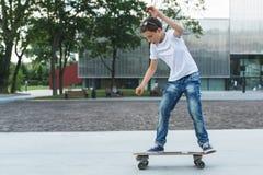 Árbol en campo El muchacho es un adolescente vestido en una camiseta blanca y los vaqueros, patinaje, haciendo engañan Foto de archivo libre de regalías