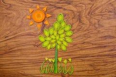 Árbol, flores y sol hechos del puerro y de rebanadas de la zanahoria en fondo de madera de la tabla de cortar Imágenes de archivo libres de regalías