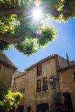 Árbol verde con la casa vieja contra el cielo azul con el sol Imagenes de archivo