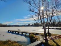 Árbol y embarcadero de Sun en el lago congelado imagenes de archivo