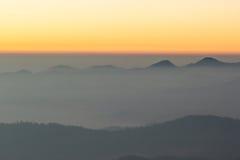 Árbol y montaña de la cubierta de la niebla de la mañana Imagen de archivo libre de regalías