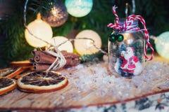 Árbol y Papá Noel de Art Christmas en un tarro de cristal delante de un Cristo Imagenes de archivo