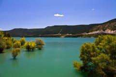 Árboles amarillos en el lago artificial de la turquesa en cielo azul en verano imágenes de archivo libres de regalías