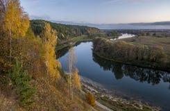 Árboles amarillos sobre el río azul Fotos de archivo