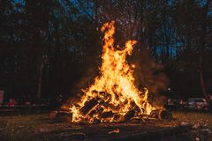 Árboles ardientes de la hoguera en la noche Llama anaranjada grande en un fondo negro Fuego en negro Brillantemente, calor, luz,  foto de archivo