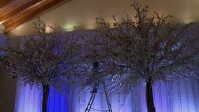 Árboles artificiales con las guirnaldas para el banquete de boda metrajes