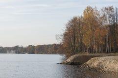 Árboles coloridos en el banco del río con ruinas viejas en fondo Fotografía de archivo