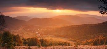 Árboles coloridos en el valle de la montaña en la puesta del sol Fotos de archivo libres de regalías