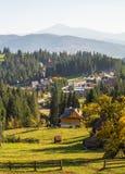 Árboles, cubiertos con las hojas amarillas y del escarlata, en las cuales las caídas calientan las montañas ligeras Cárpato, Ucra fotografía de archivo libre de regalías