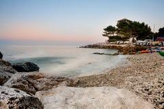 Árboles de la torre y de pino en una playa en la puesta del sol Fotografía de archivo libre de regalías
