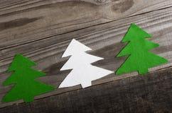 Árboles de navidad hechos del fieltro en el tablero de madera Imágenes de archivo libres de regalías