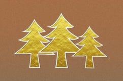 Árboles de navidad de oro en fondo metálico marrón del brillo Imágenes de archivo libres de regalías