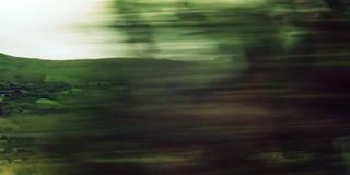Árboles Defocused vistos a través de un parabrisas del coche Imágenes de archivo libres de regalías