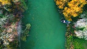 Árboles del río y del otoño y barco de pesca durante la puesta del sol, vídeo aéreo del abejón
