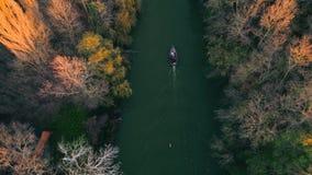 Árboles del río y del otoño y navegación del barco de pesca durante la puesta del sol, vídeo aéreo del abejón
