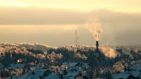 Árboles helados, tejados nevosos y tubo que fuma en la posibilidad muy remota de la puesta del sol Fotos de archivo libres de regalías