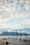Árboles muertos y playa fangosa en la puesta del sol Foto de archivo