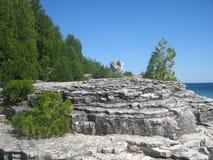 Árboles, rocas, lago y cielo azul Fotos de archivo libres de regalías