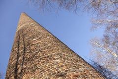 Árboles viejos de la chimenea y de abedul de la fábrica del ladrillo debajo del cielo azul Fotos de archivo