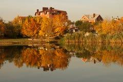Árboles y casa reflejados en el agua Fotos de archivo