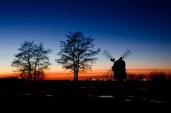 Árboles y molino de viento viejo en puesta del sol Imagen de archivo