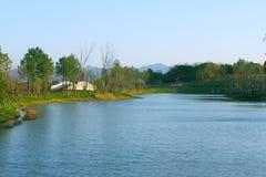 Árboles y puentes al lado del lago azulverde imagen de archivo libre de regalías