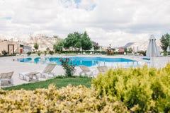 Área al lado del hotel Piscina con agua azul, los sunbeds blancos, las flores, los árboles y los arbustos contra la perspectiva d imagen de archivo