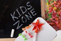 A área das crianças caçoa o espaço da zona escrito em um quadro-negro com giz, caramelo, doces, estrela, varinha, dia de Valentim Imagens de Stock Royalty Free