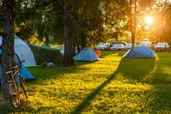 Área de acampamento das barracas no lugar natural bonito com árvores grandes e grama verde Imagens de Stock