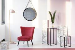 Área de assento com poltrona marrom, lâmpada, espelho, cubos de mármore Imagem de Stock